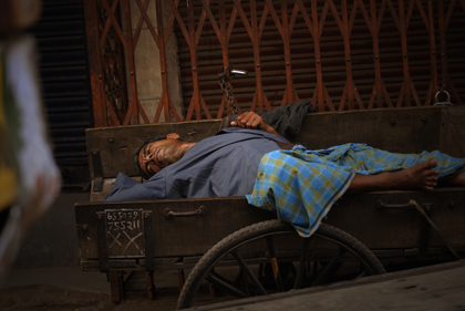 A man taking a nap in the streets of Delhi. With working hours up to 18 hours a day, a nap is well needed. Read about the sleeping man on this hand-pulled cart and the working conditions in India in this archive story.