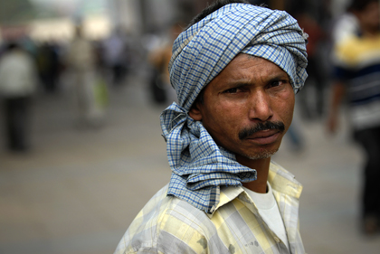 Delhi is a hot, dusty city and the combination of the two may reduce visibility in the summer, where temperatures regularly top forty degrees, as seen in this portrait of and Indian man in New Delhi. Read more about portrait photography in this archive story.
